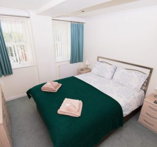 Master bedroom with a double bed, with 2 bedside tables with lamps and an alarm clock. Towels on the bed neatly folded.