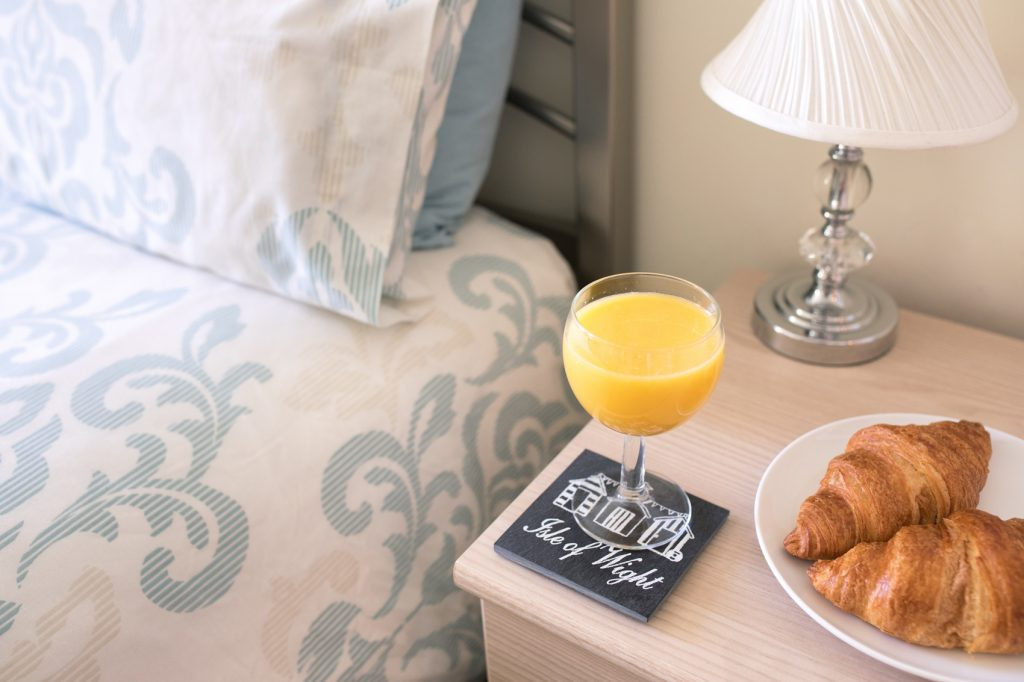 Glass of orange juice on the bedside table of the master bedroom. A plate with 2 croissants behind.