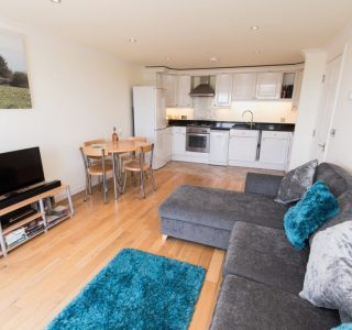 Living area, dining area and kitchen. TV on TV stand with sound bar ontop of media unit. 'L' shaped sofa.