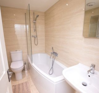 Bathroom. Sink fitted a mixer tap and mirror above. Next to that is a bath with both taps and shower head attached. Shower above with shower screen fitted around the edge of the bath