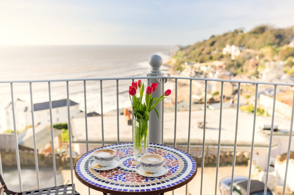 Small table with mosaic pattern with 2 cups of coffee and a vase of roses. Placed on the balcony area of Beach View overlooking Ventnor Bay