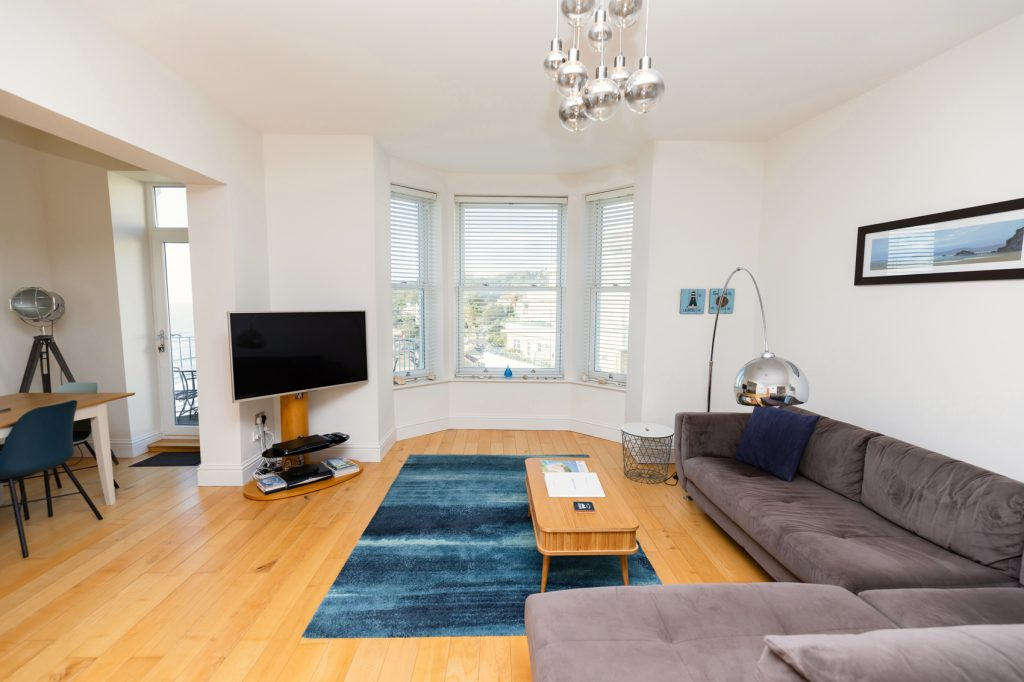Beach View living area with TV on stand in the corner. Bay Windows that face Ventnor Bay