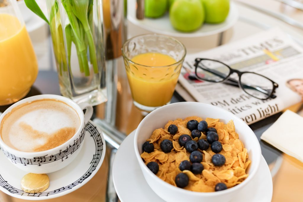 Breakfast with a glass of orange juice and a cup of coffee, resting on a copy of the local newspaper