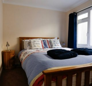 Master Bedroom with two bedside tables and a cupboard space. Window with views of Ventnor seafront