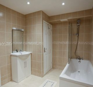 Bathroom with bath, shower and shower screen. Wash basin with mirror above.