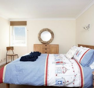 Master bedroom with bedside tables and lamps. Drawers and cupboards for stoarge space