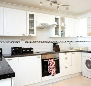 Beyond the Sea Kitchen area with oven, electric hob, extractor fan, utensils, washing mahine, fridge/freezer