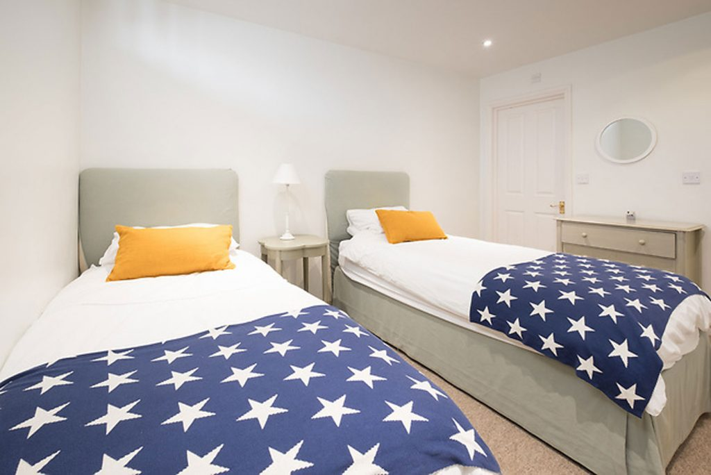 Twin Bedroom fitted with 2 single beds with stars covers, bed side table and chest of drawers