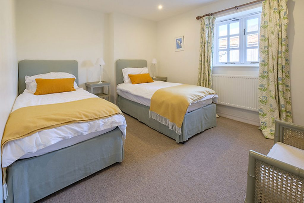 Twin room at Shalfleet Barn, two single beds with bed side tables and wardrobe/drawer space