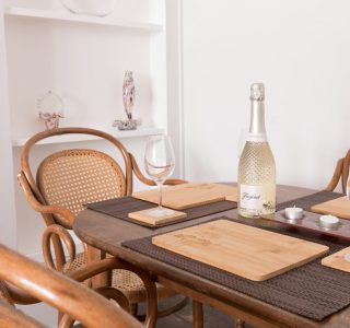 Dining table with a bottle of Freixenet Prosecco and 3 prosecco glasses, Wooden place settings and a set 4 tea light candles in the middle of the table.