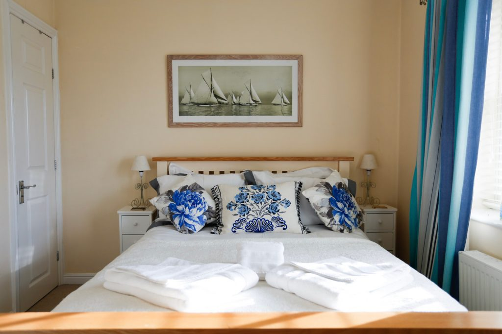 Master Bedroom, double bed with 2 bedside tables. Towels neatly folded on top of bed ready for guests
