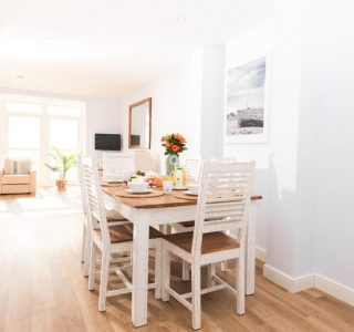 Open plan dining area with seating for 6, living area in the background