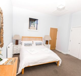 Master Bedroom with double bed bedside tables either side with lamps. a cupboard space along the right wall for storage space. chest of drawers bottom left