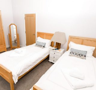 Twin room with 2 single beds. a wardrobe and bedside table