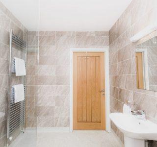 Wash basin right, heated towel rail left