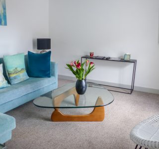Living Area with Flatscreen Smart TV mounted to wall. L shaped Sofa pictured on the left side. Curved edged three sided glass topped coffee table with a plant pot in the centre of the shot.
