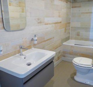 Master Bathroom, Toilet, Bath with overhead shower. Large wash basin with singular mixer tap. Mirror above wash basin.
