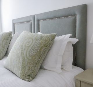 Franks master bedroom. Close up shot of the Kingsize bed. Cushions are displayed ontop of the bed.