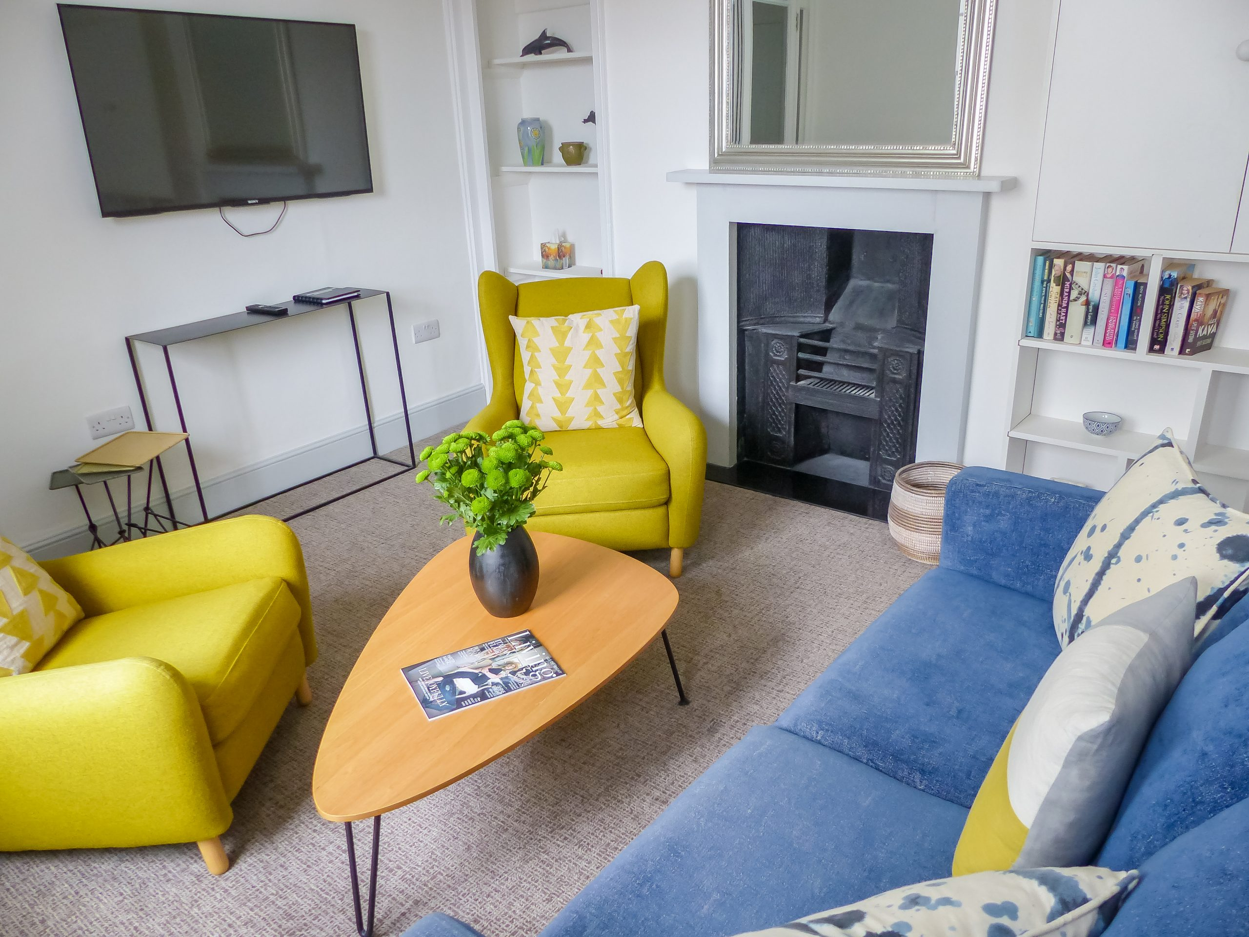 Photo of the living area, two yellow mustard arm chairs and a dark blue sofa surrounding a triangular shaped table with a vase and flowers on top.