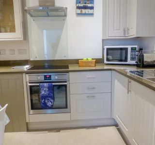 Paskins kitchen area, fitted with electric oven and hob, dishwasher, washing machine, microwave and toaster. Kettle and tea/coffee making facilities are pictured left.
